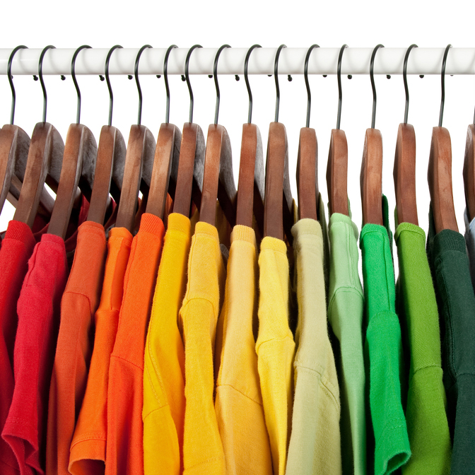 Rainbow T-shirts on wooden hangers