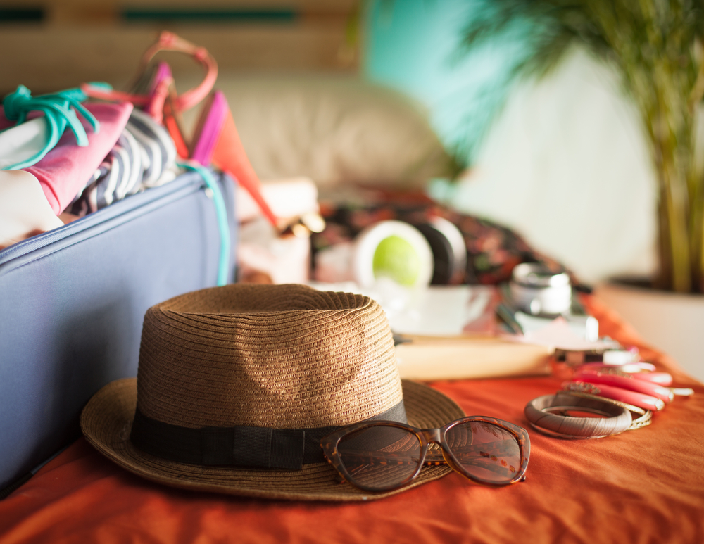 Woman's bedroom full of things ready to be taken on summer vacation