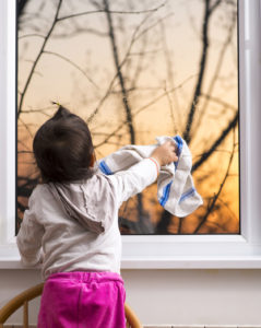 Little girl rubbing glass with cloth on window