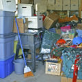 A very messy garage with clutter and storage boxes in portrait orientation.
