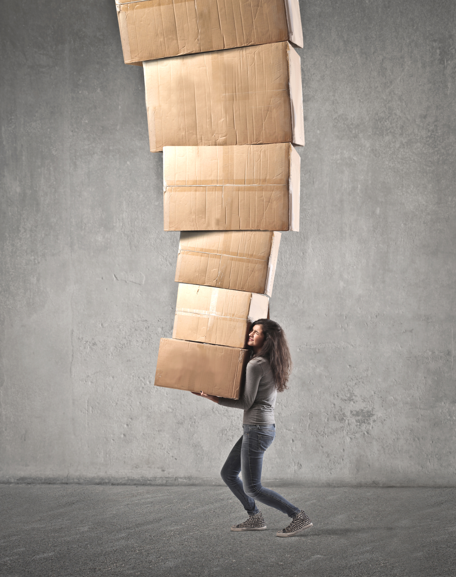 Woman carrying enormous stack of moving boxes