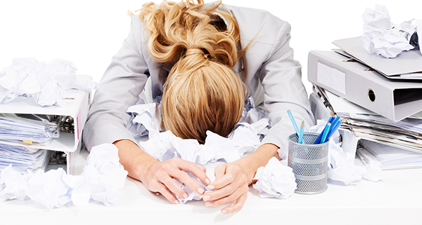 Overwhelmed woman, head down in paper clutter on desk