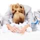 Overwhelmed woman, head down in paper clutter on desk