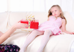 Little girl reluctantly receives a holiday gift